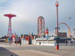 Coney Island Boardwalk (Mildred Alpern) Tags: coneyisland boardwalk amusements steeple thunderbolt passersby shadow