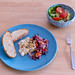 Gebackener Hirtenkäse an Tomatengemüse dazu Knoblauchfladenbrot auf einem blauen Teller und ein frischer Salat