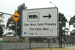 'Take West Gate Freeway - The Easy Way' sign targeted at truck drivers from the Port of Melbourne (Marcus Wong from Geelong) Tags: westgatebridge bridge road freeway melbourne spotswood yarrariver fishermansbend boxgirder m1 cablestayed cablestayedbridge loweryarracrossing portmelbourne