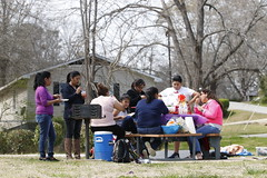 Members of Silvìa Abila's dance group sitting at a picnic table eating Mexican food. Abila's dance group practices in Robinson Park because they cannot afford to rent a room to practice in.