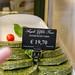 Grüne, vegetarische Hamburger Pattys, dekoriert mit Tomate, angepriesen mit schwarzem Preisschild in Verkaufsauslage