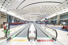 Hong Kong International Airport Gates 2 (ArdieBeaPhotography) Tags: airport gates travellator conveyorbelt rowsofchairs chairs seats clean white glow geometric pattern ceiling arched arcs triangular blue carpet passengers waiting windows night light bright flourescent wideangle