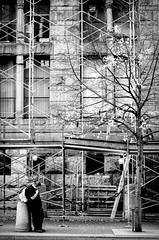 Lonely Stop (Nathan Gentry) Tags: blackandwhite photography photographer shootfilm film 35mm 35mmphotography filmphotography analog canon canontlb ilford busstop lady lonely alone construction waiting tree dramatic pittsburgh scaffold scaffolding pennsylvania