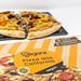 Vegane Holzofen-Pizza geviertelt auf Steinplatte vor Pizzakarton von Veganz