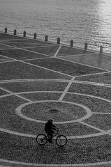 [ Eliocentrismo - Heliocentricity ] DSC_0069.R2.jinkoll (jinkoll) Tags: street geometry kid child blackandwhite bnw bw bn sea mare waves reflections square city reggio calabria circle bike biker bicycle rider riding afternoon sunset passing passerby alone solitude peace serenity shadows bricks
