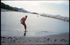 (A Jump Start) (Robbie McIntosh) Tags: leicamp leica mp rangefinder streetphotography 35mm film pellicola analog analogue negative leicam elmarit analogico leicaelmarit28mmf28iii elmarit28mmf28iii dyi selfdeveloped filmisnotdead autaut candid bellinifotoc41 kodakportra160 kodakportra portra kodak beach tan seaside bathers strangers swimsuit lidomappatella mappatellabeach man summer summertime speedo dive jump