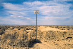 no dumping. mojave desert, ca. 2012. (eyetwist) Tags: eyetwistkevinballuff eyetwist nodumping sign minimalist landscape empty mojavedesert california nikon n90s nikkor 28105mmf3545d fuji velvia 50 rvp transparency chrome slide nikonn90s fujivelvia50rvp ishootfilm ishootfuji analog analogue film emulsion coolscan 35mm 28105mm iconla southwest usa type typography typographic street road roadsideamerica lancaster post dirt horizon desert void vast penalcode publicworks environment trash