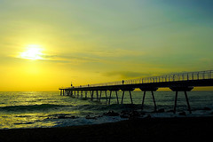 Sunrise - Some go others come (Fnikos) Tags: sea water mar mare wave ocean landscape seascape coast beach bay shore seashore sand dark light bridge puente pont pier sun sunrise cloud architecture construction rock sky skyline people outdoor