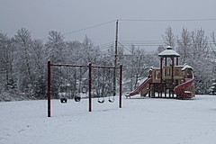 Winter Playground (sarah-sari19) Tags: april spring snow snowy white outside outdoors weather nature fresh clean snowing snowflakes trees branches playground colour empty red green yellow slide swings play