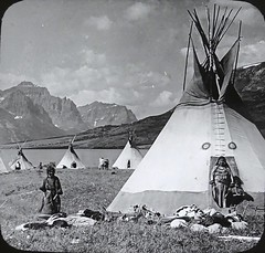 """Indian Village, Reservation, Glacier National Park."" (ca. 1920s). Lantern Slide Image P252 (V23181), Keystone View Company (lhboudreau) Tags: nativeamericans lanternslide nativeamerican americanindian vintagephoto vintagephotograph vintagephotography monochrome blackandwhite blackwhite indianvillage 1920 1920s image keystone keystoneview keystoneviewcompany slidep252 v23181 outdoor outdoors indian photo antiquephoto tipi teepee teepees tipis water mountain mountains people indians americanindians dwelling shore landscape slide indianreservation glaciernationalpark montana hides skins village lake sky clouds cloud squaw papoose squaws indianwomen indianwoman"