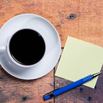 Cup of coffee and a sticky note with empty space for a text on wooden background thumbnail
