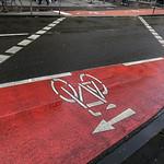 Rot markierter Fahrradweg führt von einer Straßenseite zur anderen thumbnail