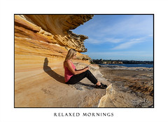 Woman sitting under sandstone rock ledge by the ocean (sugarbellaleah) Tags: woman female ledge rock sandstone girl blonde nature seascape lifestyle morning sitting timeout chillingout relaxed communication technology phone mobilephone cellphone textmessage sms reading looking sydney australia networking