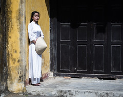Hoi An 11 (arsamie) Tags: hoi an vietnam asia nonla non la ao dai aodai woman girl street urban pose white dress traditional folklore yellow paint wall house door brown people portrait