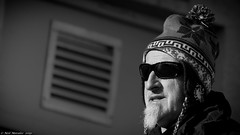 Now whats that all about (Neil. Moralee) Tags: neilmoralee man old mature beard goatee sunnie sun glasses shadows bright street candid hat pompom pom tassles black white bw bandw blackandwhite mono monochrome nikon d7200 neil moralee beer devon uk odd face portrait