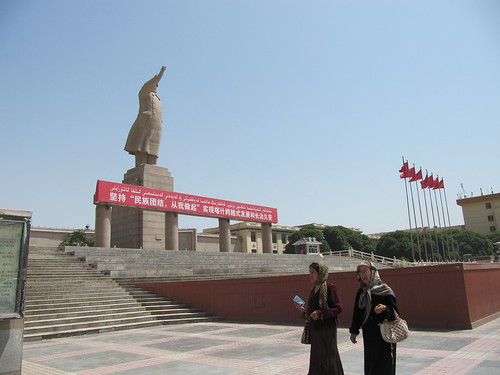 Women walk past a statue of Mao.  Kashgar, Xinjiang, China