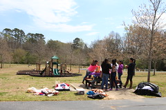 Members of Abila's dance group around a picnic table. Abila's dance group practices in Robinson Park because they cannot afford to rent a room to practice in.