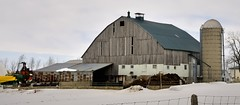 Operating farm with large unpainted barn - Wellington County, Ontario. (edk7) Tags: nikond300 edk7 2013 canada ontario wellingtoncounty farm barn silo weatheredwood rustycorrugatedgalvanizedsteelshed architecture building oldstructure winter snow field manurepile fence house gambrelroofline equipment implements