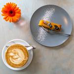 Kürbiskuchen auf einem Teller und eine Tasse Cappuccino mit einer Blume in der Aufsict thumbnail
