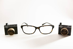 Two camera crafts and reading glasses (wuestenigel) Tags: lenses craft photography camera two glasses background reading white lens linse eyeglasses brille plastic kunststoff equipment ausrüstung isolated isoliert retro eyesight sehvermögen electronics elektronik vintage jahrgang technology technologie eyewear brillen modern noperson keineperson optics optik desktop classic klassisch accessory zubehörteil optometry optometrie sunglasses sonnenbrille movie film