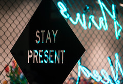 Stay Present - L.A. Art Show 2019 (ChrisGoldNY) Tags: losangeles la california iphone bookcover albumcover licensing forsale chrisgoldphoto chrisgoldberg chrisgoldny sonyimages sonya7rii sonyalpha laartshow dtla angeleno art artshow exhibit exhibits signs blue light neon chainlink black