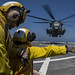 Sailor signals to CH-53E helicopter pilots before taking off.