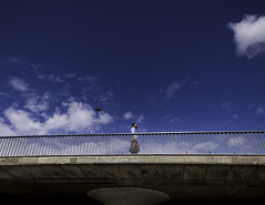 Walking on a Bridge (Leon Sammartino) Tags: streetphotography bridge copenhagen denmark sky classic clouds blue fujifilm