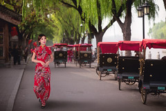 Chinese lady in red cheongsam dress walking near a Tourists riding Beijing traditional rickshaw (anekphoto) Tags: beijing china hutong rickshaw old traditional riding red people vacation travel vintage retro tourist tree outdoor house tourism leisure culture ancient asian asia road street chinese destination oriental sit ethnicity sightseeing bicycle driving traveler taxi city urban republic peoples hutongs tourists nature architecture lady woman walk dress happy newyear cheongsam