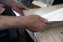 Curtis turns the pages of a family record in his home. This house holds all sorts of records of births, deaths, sales, and all parts of his family's history that they have preserved over the years.