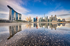 Ponding in the city (Scintt) Tags: singapore mbs marina bay water sky dramatic travel tourist attraction exploration movement motion skyline cityscape city urban modern structures architecture buildings offices shenton way cbd scintillation scintt jonchiangphotography iconic surreal epic wideangle still calm glow light tones nature pond pool waterfront sands raffles place puddle rain golden warm orange yellow symmetrical mirror reflection sun sunstar lowangle clouds financial centre jogger exercise tourism morning early dawn sunrise