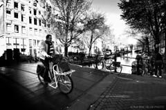 Hard Light-BP30483bw (Rob Blok / BLOK PHOTO) Tags: street canal bridge cyclist amsterdam amsterdamstreetphotography nikon dx 1224mm blackwhite highcontrast blokphoto robblokphotography robblokfotografie