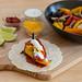 Die Hellofresh Vegetarische Fajita mit Paprika & Pilzen, selbst gemachter, scharfer Soße und Limettenschmand auf einem Holzbrett mit den Zutaten