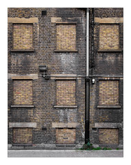 The Built Environment, East London, England. (Joseph O'Malley64) Tags: thebuiltenvironment newtopography newtopographics manmadeenvironment manmadestructure building architecture architecturalfeatures architecturalphotography victorian victorianbuilding documentaryphotography britishdocumentaryphotography eastlondon eastend london england uk britain british greatbritain londonbrick brickwork bricksmortar cement pointing lintels concrete reinforcedconcrete glazedbricks airbricks vents brickedup brickedupwindows windowsills changeofuse recesseddrainpipe drainpipe castirondrainpipe plasticdrainpipe drainpipes cctv cctvcamera lamp lighting securitylighting electricalconduit wiring electricalwiring render tarmac weeds vegetation disappearinglondon oldlondon lostlondon patina waterdamage frostdamage coalsootdamage acidraindamage hygroscopicsaltsinbrickwork weathering urban urbanlandscape fujix fujix100t accuracyprecision