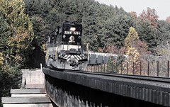 Norfolk Southern (a former Southern Railway engine) EMD SD40-2 # 3264, along with two other engines, are seen on a main line curved bridge while leading a manifest freight train in a location between Harriman and Chattanooga, Tennessee, October 1987 (alcomike43) Tags: norfolksouthern norfolkwestern railfanexcursiontrain freighttrains passengertrains railroads trains harrimanjunction chattanoogatennessee mainline rails ties roadbed ballast weldedribbonrail curvedrailroadbridge steeldeckrailroadbridge rightofway countryside forest trees fallleafcolors scenic landscape coveredhoppercars engines diesels locomotives dieselengine diesellocomotive emd sd402 3264 dieselelectriclocomotive photo photograph slide color old historic vintage classic