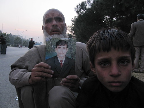 Minhaj Khan, from Buner, Pakistan, holds a picture of his son, 35 year old Bakhu Ali Khan, a missing person, presumed in Pakistani custody, at a protest in Islamabad, Pakistan.
