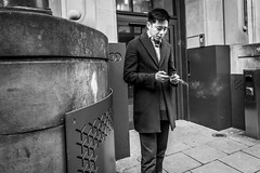 Cigarette Smoke (Leanne Boulton) Tags: urban street candid portrait portraiture streetphotography candidstreetphotography candidportrait streetportrait streetlife hipshot man male face expression mood mobile phone smartphone smoke smoker smoking cigarette doorway tone texture detail depth naturallight outdoor light shade city scene human life living humanity society culture lifestyle people canon canon5dmkiii black white blackwhite bw mono blackandwhite monochrome glasgow scotland uk