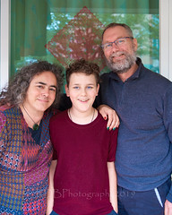 Whanau of Three (ArdieBeaPhotography) Tags: family three mother father son boy preteen embrace portrait maroon tshirt geometric patterned top grey knitted jumper zipped poloneck glass door window reflection tree paper cutout decoration chinese character man woman beard glasses blue eyes curly hair pounamu greenstone pendant koru painted nails