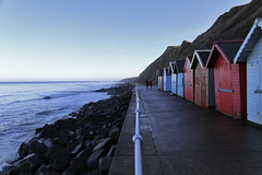 Sheringham Promenade (_ _steven.kemp_ _) Tags: sheringham seaside norfolk england sea beach hut rocks seats promenade bench coast coastal red blue strangers people walking metal fence post cliff