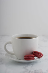 2 chocolate french macarons with a cup of coffee on a white marble table. (brian_barney9021) Tags: coffee dessert french bakery food macaron sweet macaroon cup cafe biscuits biscuit white delicious meringue table gastronomy treat pastries macarons light fresh gourmet mug background baked tasty chocolate drink brown confectionery plate beverage cookie good beautiful sugar drinking morning cookies kitchen confection copyspace pastry