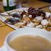 Kaiserschmarrn mit Zwetschgen, Apfelmus und Puderzucker mit mehreren Löffeln auf Holztisch