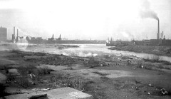 Places that Manhattan tourists DIDN'T visit. Standing in Long Island City, Queens, looking west to the Newtown Creek and some of the factories which lined its shores. One of the Greenpoint gas tanks at left. New York. 1934 (wavz13) Tags: newyorkphotographs newyorkphotos urbanphotography urbanphotos newyorkphotography oldphotographs oldphotos 1930sphotographs 1930sphotos oldphotography 1930sphotography vintagenewyorkphotography vintagenewyorkphotographs vintagenewyorkphotos oldnewyorkphotography oldnewyorkphotographs oldnewyorkphotos depressing bleak noir noire dark urbanscenes cityphotography cityphotos vintageindustry oldindustry vintageindustrial oldindustrial vintagefactory oldfactory vintagefactories oldfactories urbanwasteland urbanblight oldsmokestacks oldsmokestack smokestacks smokestack industrialwasteland wasteland industry industrial bleakwasteland pollution polluted brownfield brownfields abandoned desolate desolation industrialphotos industrialphotography vintageemulsions 1930semulsions