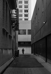 Biker in the alley (lensesofi) Tags: cityscapes black white biker alleys buildings moody