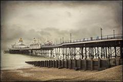 Eastbourne Pier(UK) (williamwalton001) Tags: pentaxart texture timber sky colourimage clouds coastal pier pebbles beach seaside historic building