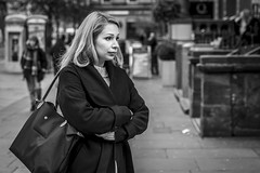 Patiently Waiting (Leanne Boulton (Away)) Tags: portrait urban street candid portraiture streetphotography candidstreetphotography candidportrait streetportrait streetlife woman female girl face eyes expression folded arms gesture mood emotion feeling blonde pretty tone texture detail depthoffield bokeh naturallight outdoor light shade city scene human life living humanity society culture lifestyle people canon canon5dmkiii 70mm ef2470mmf28liiusm black white blackwhite bw mono blackandwhite monochrome glasgow scotland uk