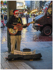 What Santa does for  a Little Spare Change (prima seadiva) Tags: dusk evening holidays market pikeplace rainy santa downtown mask busker