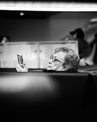 Airport lounging (jameswilkinson1) Tags: streetpassionaward streetphotography street 50mm summilux m10 leica traveling travel phone woman people airport blackandwhite bnw