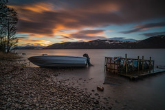 Abandoned. (Gordie Broon.) Tags: lochness speedboat abandoned le dores thegreatglen sunset beach scotland scottishhighlands paysage schottland scenery paisaje ecosse caledonia winter 2019 escocia sky clouds scenic scozia lago lac landscape hills collines colinas hugeln inverness inverfarigaig northernscotland gordiebroonphotography meallfuarmhonaidh silhouettes scenario szkocja scaniport glenalbyn sonya7rmkii ilce7rm2 sonyzeiss1635f4lens geotagged heuvels giottos january