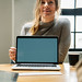 Happy woman with a blank laptop screen