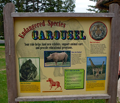 Endangered Species Carousel Sign. (dccradio) Tags: greenbay wi wisconsin browncounty sky overcast outdoor outdoors outside tree trees greenery fuji finepix a900 sign words text gorilla gorillas rhino rhinoceros blackrhino blackrhinoceros giraffe rothschilds masai tiger siberian zebra grass lawn yard post signpost