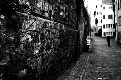 Heavy walls for the city (Leica M6) (stefankamert) Tags: wall heavy film analog grain blackandwhite blackwhite noiretblanc noir analogue leica m6 leicam6 summicron dr dualrange textures man people blur blurry highcontrast stefankamert street kodak trix tübingen city town old cobblestones dark